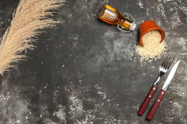 Vista superior do arroz fresco cru com talheres na superfície escura da foto do óleo