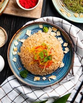 Vista superior do arroz japonês frito com legumes em molho de soja em um prato na superfície de madeira