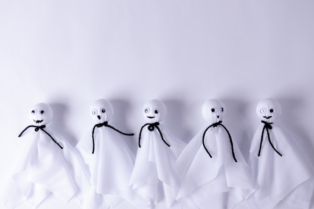 Vista superior do artesanato de halloween, fantasma de papel em papel branco fundo com copyspace