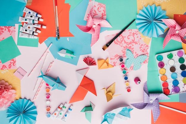Vista superior do artesanato de origami; tubo de tinta; pincel; palha e papel colorido