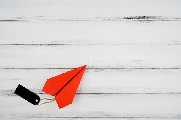 Vista superior do avião de papel vermelho com etiqueta no fundo de madeira