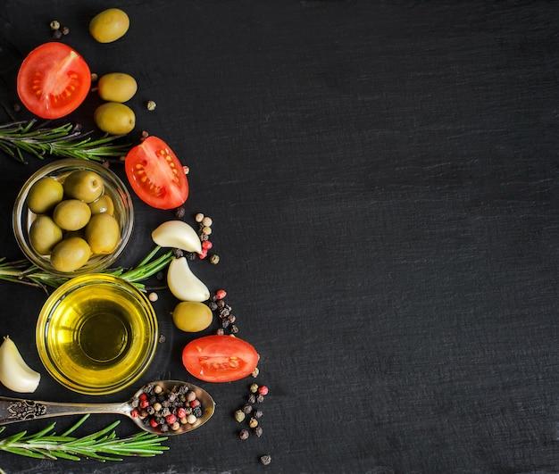 Vista superior do azeite e ingredientes para uma salada vegetariana saudável - tomate cereja, azeitonas, alho e alecrim no fundo da ardósia preto natural com copyspace