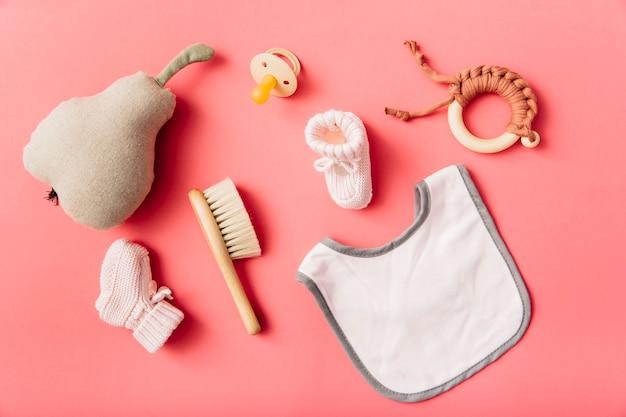 Vista superior do babador do bebê; chupeta; meia; escova; pêra recheada e brinquedo em fundo de pêssego