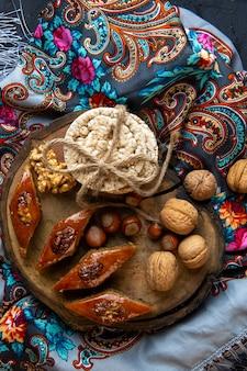 Vista superior do baklava tradicional do azerbaijão com nozes inteiras e pães de arroz em um xale com borla