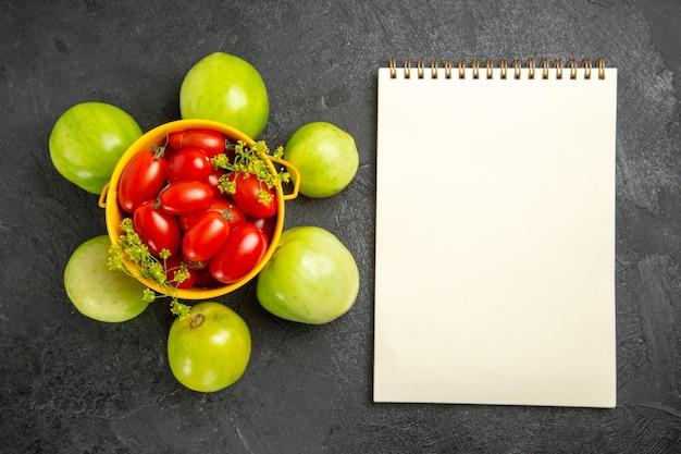 Vista superior do balde amarelo cheio de tomates cereja e flores de endro cercado de tomates verdes e um caderno em solo escuro