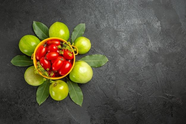 Vista superior do balde amarelo cheio de tomates cereja e flores de endro cercado de tomates verdes em um solo escuro com espaço livre