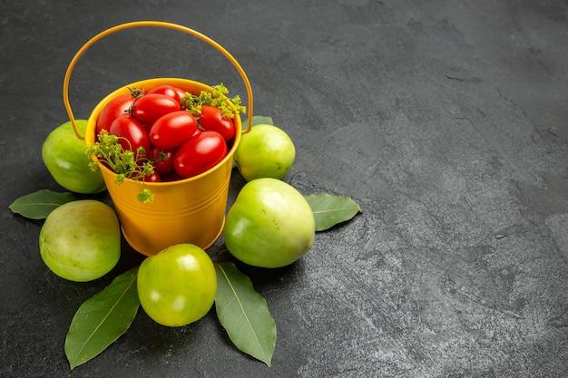 Vista superior do balde amarelo cheio de tomates cereja e flores de endro cercado de tomates verdes na superfície escura