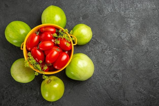 Vista superior do balde amarelo cheio de tomates cereja e flores de endro e arredondado com tomates verdes na superfície escura