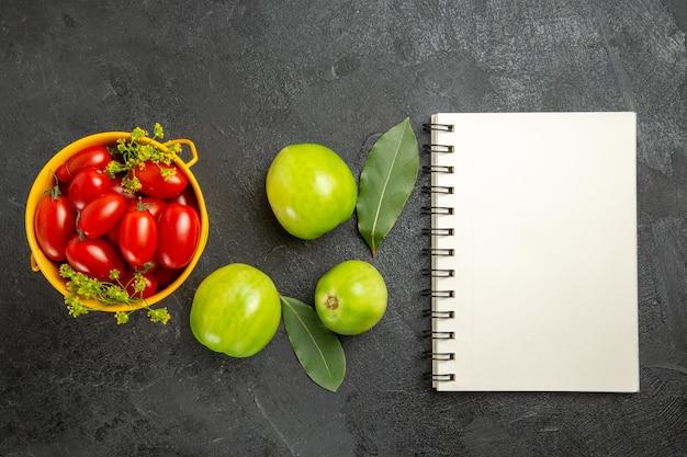 Vista superior do balde amarelo cheio de tomates cereja e flores de endro, folhas de louro, tomates verdes e um caderno em solo escuro com espaço de cópia