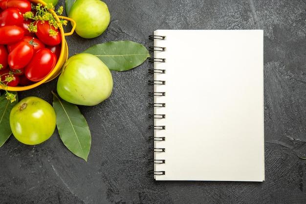 Vista superior do balde amarelo cheio de tomates cereja e flores de endro, folhas de louro, tomates verdes e um caderno na superfície escura
