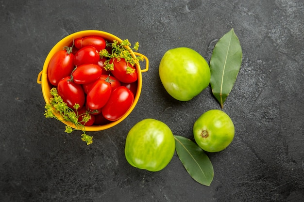 Vista superior do balde amarelo cheio de tomates cereja e folhas de louro com flores de endro e tomates verdes em um solo escuro com espaço de cópia