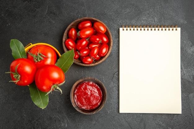Vista superior do balde amarelo com tomates e folhas de louro tigelas com tomate cereja e ketchup e um caderno em solo escuro
