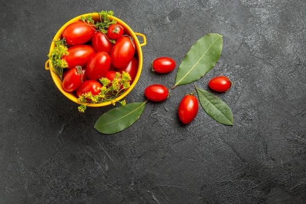 Vista superior do balde amarelo de tomate cereja e folhas de louro com flores de endro e tomate cereja no chão escuro com espaço de cópia