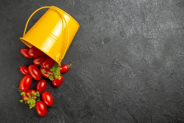 Vista superior do balde amarelo virado cheio de tomates cereja e flores de endro à esquerda de um terreno escuro com espaço de cópia