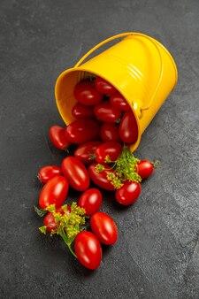 Vista superior do balde amarelo virado cheio de tomates cereja e flores de endro no chão escuro