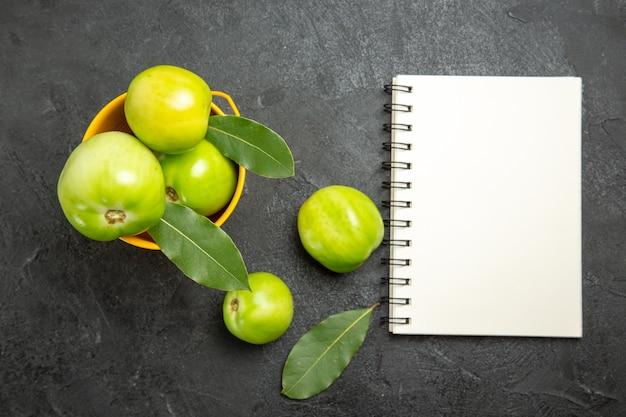 Vista superior do balde de tomates verdes e folhas de louro, um caderno e tomates em fundo escuro
