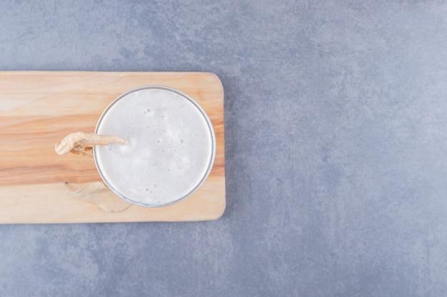 Vista superior do batido de leite acabado de fazer na tábua de madeira.