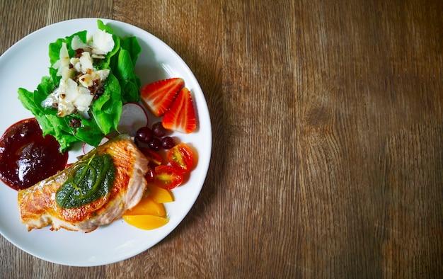 Vista superior do bife de salmão grelhado closeup com salada e molho de morango