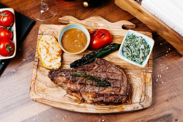 Vista superior do bife grelhado servido com legumes e molho em uma placa de madeira