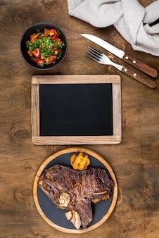 Vista superior do bife no prato com salada e quadro-negro