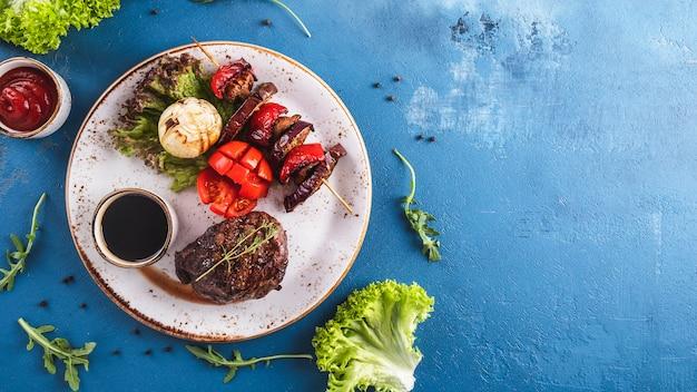 Vista superior do bife suculento grelhado com legumes em um prato.