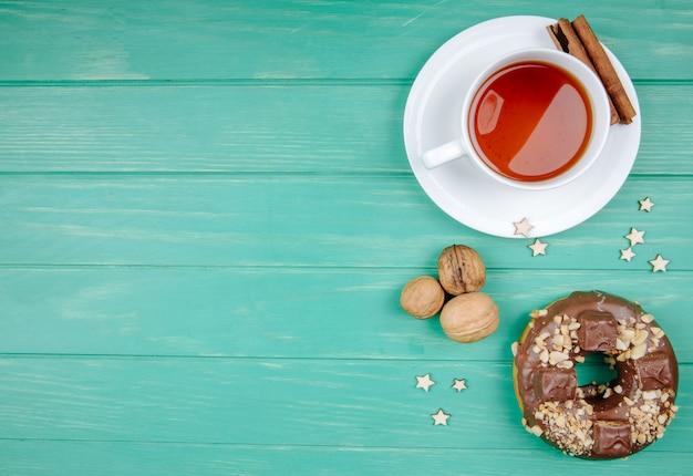 Vista superior do biscoito de chocolate e xícara de chá com canela no saquinho de chá com nozes no verde com espaço de cópia
