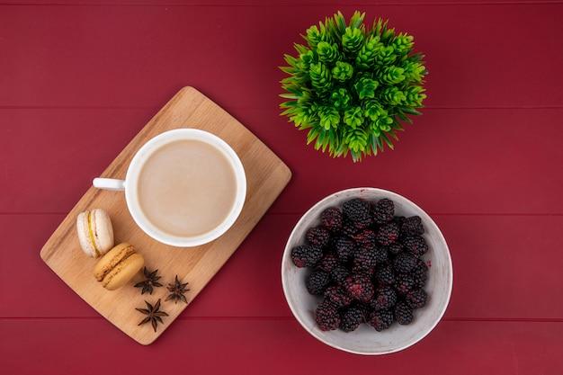 Vista superior do blackberry com uma xícara de cappuccino com macarons em uma placa de corte em uma superfície vermelha