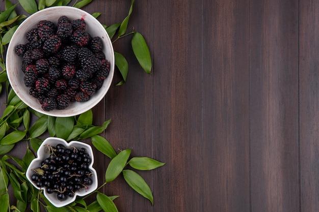 Vista superior do blackberry em uma tigela com groselha preta e ramos de folhas em uma superfície de madeira