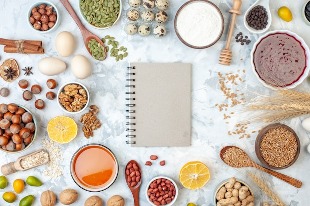 Vista superior do bloco de notas cinza com ovos de geleia, nozes e sementes diferentes na massa branca, bolo de nozes, torta doce, coração, foto, açúcar