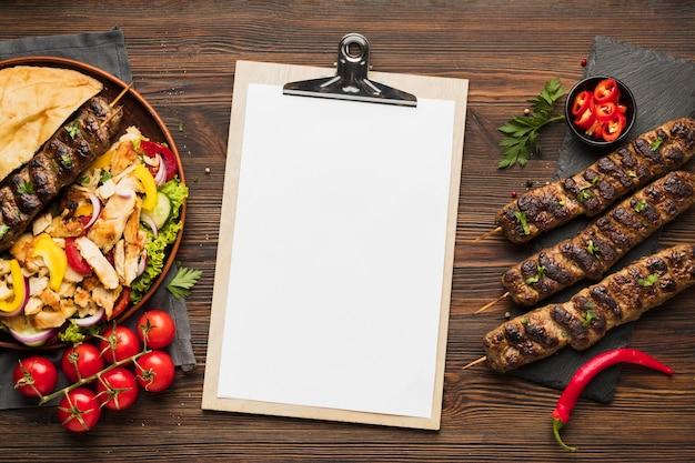 Vista superior do bloco de notas com deliciosos kebabs e tomates