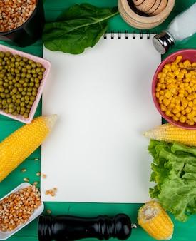 Vista superior do bloco de notas com grãos de milho sementes de ervilhas espinafre alface e sal ao redor no verde com espaço de cópia