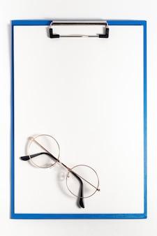 Vista superior do bloco de notas com óculos em cima