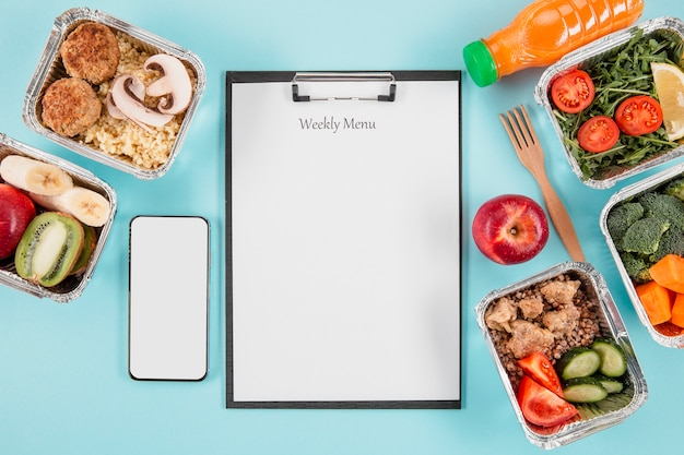 Vista superior do bloco de notas com refeições e smartphone