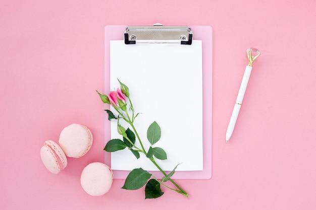 Vista superior do bloco de notas com rose e macarons