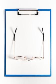 Vista superior do bloco de notas com um par de óculos na parte superior