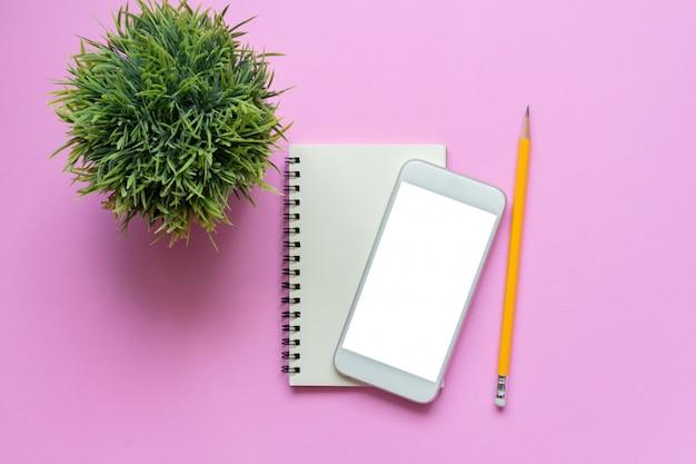 Vista superior do bloco de notas de smartphone maquete, lápis e planta em rosa