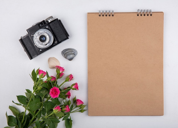 Vista superior do bloco de notas e da câmera fotográfica com flores e conchas no fundo branco com espaço de cópia