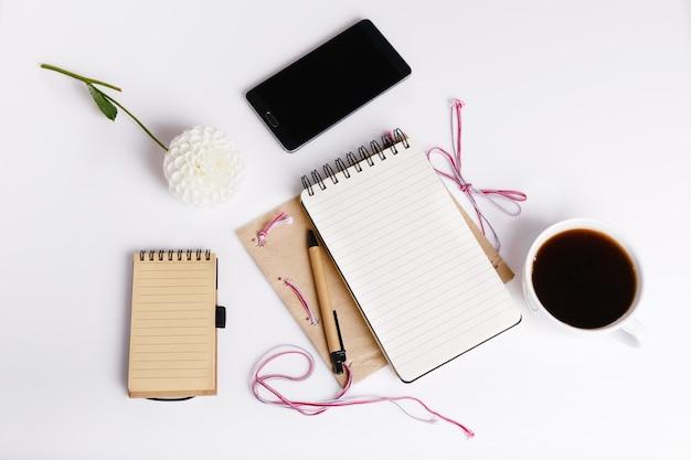 Vista superior do bloco de notas em branco na mesa de escritório branca com smartphone, bloco de notas, caneta, flor dália branca e xícara de café. camada plana, vista superior