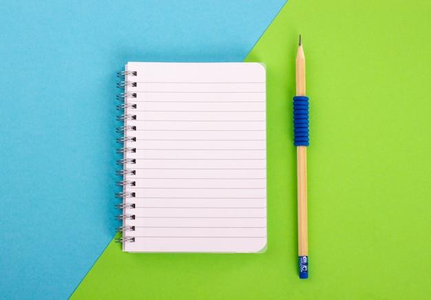 Vista superior do bloco de notas espiral e do lápis de madeira no fundo azul esverdeado. estilo leigo plano.