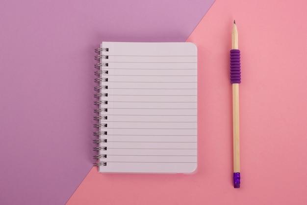 Vista superior do bloco de notas espiral e do lápis de madeira no fundo da cor-de-rosa-alfazema. estilo leigo plano.