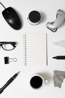 Vista superior do bloco de notas espiral em branco com artigos de papelaria do escritório; xícara de café; óculos sobre a mesa branca