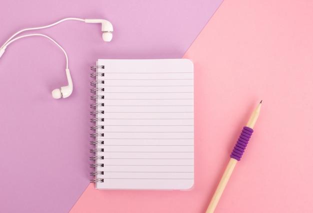 Vista superior do bloco de notas espiral, lápis de madeira e fones de ouvido no fundo pastel rosa.