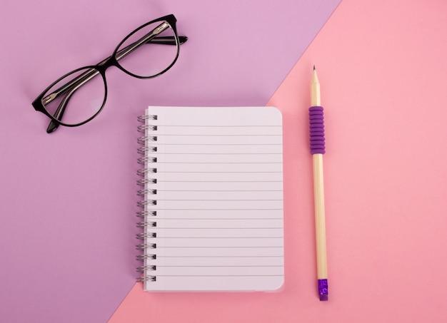 Vista superior do bloco de notas espiral, lápis de madeira e óculos em fundo rosa-lavanda. la plana