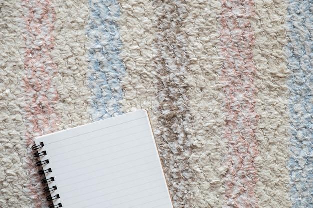 Vista superior do bloco de notas vazio na toalha de mesa, copie o espaço