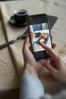 Vista superior do blogueiro tirando fotos da xícara em seu smartphone