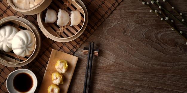 Vista superior do bolinho chinês cozido no vapor e pão de porco cozido no vapor em um vaporizador de bambu com pauzinho na mesa de madeira