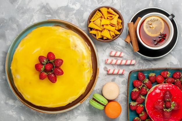 Vista superior do bolo amarelo com bolo de morango e xícara de chá no fundo branco