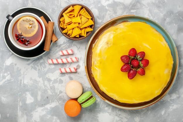 Vista superior do bolo amarelo com macarons e uma xícara de chá no fundo branco