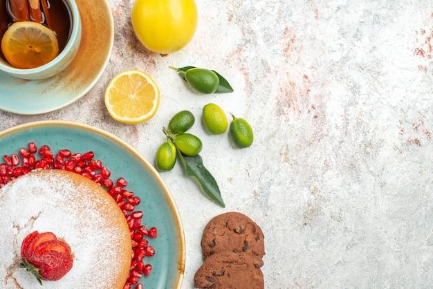 Vista superior do bolo apetitoso uma xícara de chá preto com limão ao lado do prato de bolo com morangos e biscoitos de romã na mesa