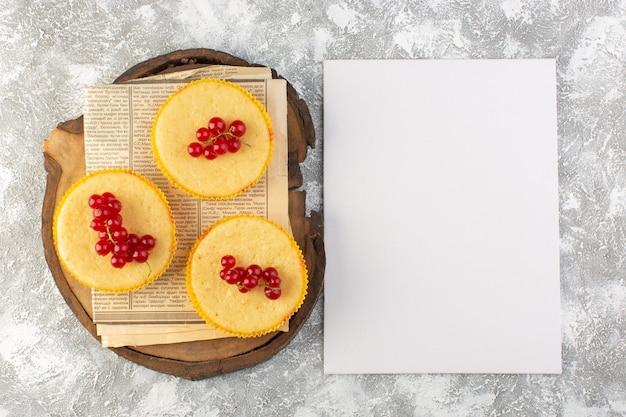 Vista superior do bolo com cranberries gostoso assado com papel em branco no fundo claro bolo biscoito açúcar doce assar
